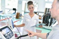 Пациент женского доктора посещая мужской в оздоровительном центре Стоковые Изображения