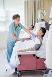 Пациент заволакивания медсестры проходя ренальный диализ Стоковая Фотография RF