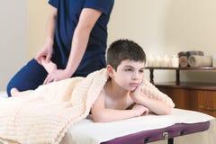 Пациент мальчика на приеме на профессиональном masseuse Терапия массажа ноги стоковое изображение rf
