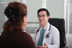 Пациент молодого доктора советуя с на офисе доктора стоковые изображения rf