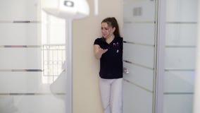 Пациент молодой женщины приходит к зубоврачебному офису сток-видео