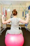 Пациент молодой женщины делая физические упражнения в исследовании реабилитации Стоковое Фото