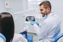 Пациент обсуждая при дантист смотря рентгеновский снимок стоковые изображения