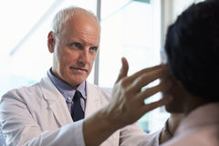 Пациент доктора В Бел Пальто Examining женский в офисе Стоковая Фотография