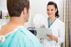 Пациент доктора С Доски сзажимом для бумаги Smiling На Стоковые Изображения RF