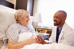 Пациент доктора Talking К Старш Женск в больничной койке Стоковое Изображение