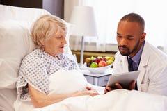 Пациент доктора Talking К Старш Женск в больничной койке Стоковое Изображение RF