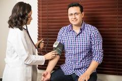 Пациент получая его давление проверенный Стоковое фото RF