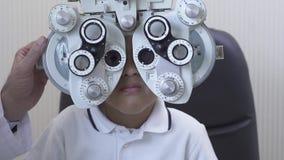 Пациент Optometrist рассматривая мужской на phoropter в клинике офтальмологии Афро-американский мальчик делая тест глаза медленны сток-видео