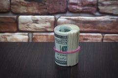 Пачка американских долларовых банкнот 100 долларов на деревянном столе около кирпичной стены Стоковое Изображение RF