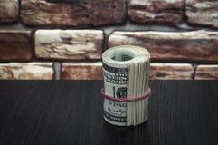 Пачка американских долларовых банкнот на деревянном столе около кирпичной стены Стоковые Фото