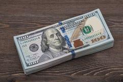 Пачка деноминаций 10 тысяч американских долларов на фоне деревянного стола Прифронтовая сторона Стоковые Фото