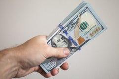Пачка 100 долларов примечаний в мужской руке Стоковая Фотография