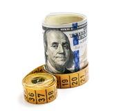 Пачка долларов подпоясала измеряя ленту на белой предпосылке Стоковое Изображение