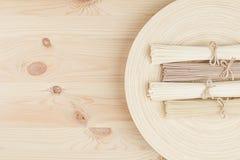 Пачки ассортимента сырцовых азиатских лапшей на бежевом деревянном блюде на деревянной доске, взгляд сверху Стоковое фото RF