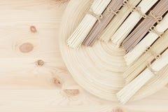 Пачки ассортимента сырцовых азиатских лапшей на бежевом деревянном блюде на деревянной доске, взгляд сверху Стоковые Фото