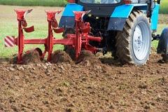 Паша трактор на работе культивирования поля стоковое фото