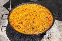 Паэлья морепродуктов Национальное испанское блюдо паэлья в большом skillet сварено на открытом огне, на коле стоковое изображение