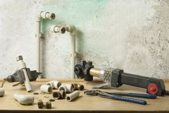 Паяя утюг для пластичных труб на деревянном столе на старой предпосылке стены Стоковые Фото