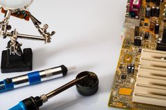 Паяя утюг, инструмент припоя удаления, материнская плата Доска анализа электронная через лупу стоковая фотография rf