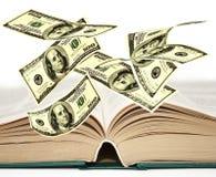 Падая примечания доллара США на начатой книге Стоковая Фотография