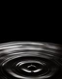 Падая пузырь воды Кольца развевают на черной брызгая предпосылке Жидкостный выплеск, мягкий космос экземпляра фокуса Стоковое фото RF