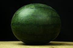 Падение арбуза большое на древесине, на черной предпосылке Стоковые Фото
