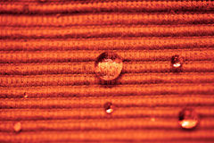 Падение воды макроса на покрашенной ткани Стоковые Фото