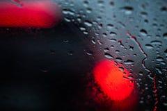 Падения дождя на стекле, в defocus красных светов автомобилей Стоковая Фотография RF