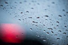 Падения дождя на стекле, в defocus красных светов автомобилей Стоковые Изображения