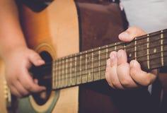 Палец гитары игры мальчика в винтажном тоне изображения Стоковое Изображение RF
