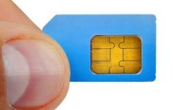 Палец держа карточку sim Стоковая Фотография RF