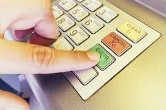 Палец женщины отжимает входит в на ATM Стоковая Фотография
