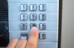 Палец нажимая кабину кнопки телефона общественную, металлические кнопки стоковые фото