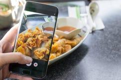 Палец отжимая на smartphone для еды фотоснимка китайской в res Стоковые Фото