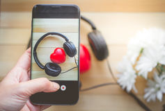 Палец отжимая на smartphone для сердца фотоснимка слушает музыка Стоковое фото RF