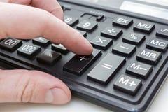 Палец пинает кнопку на калькуляторе стоковая фотография