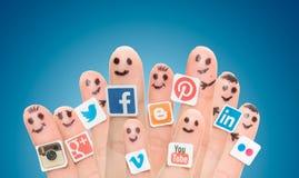 Палец с популярными социальными логотипами средств массовой информации напечатал на бумаге стоковые изображения
