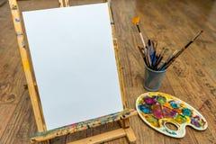 Палитра и щетки мольберта с пустым белым холстом Стоковое Фото