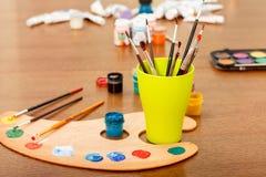 Палитра с класть на краски и чашку с paintbrushes Стоковые Фотографии RF