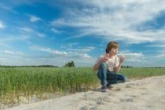 Палочка пузыря мыла кавказского подростка дуя для делать пузыри мыла на дороге поля овса грязи Стоковые Изображения