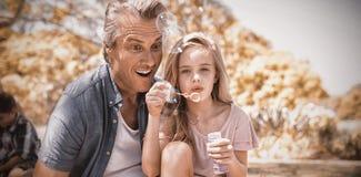 Палочка пузыря отца и дочери дуя на пикнике в парке Стоковая Фотография RF