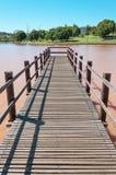 Палуба сделанная из деревянных доск на воде озера в парке с деревьями и зеленой предпосылкой вегетации Стоковые Изображения RF