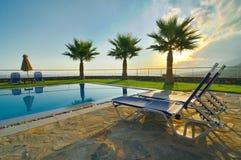 Пальмы и бассейн в эгейском восходе солнца стоковые фото
