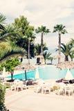 Пальмы, sunbeds пляжа и зонтики Стоковое Изображение