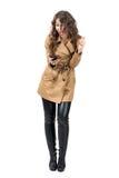 Пальто восторженной молодой женщины нося смотря мобильный телефон Стоковые Изображения
