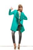 Пальто женщины зеленое делая большой палец руки вверх по знаку Стоковые Изображения RF