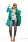 Пальто женщины зеленое делая большой палец руки вверх по знаку Стоковое Изображение