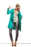 Пальто женщины зеленое делая большой палец руки вверх по знаку Стоковое фото RF