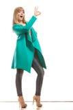 Пальто женщины зеленое делая одобренный знак Стоковое фото RF